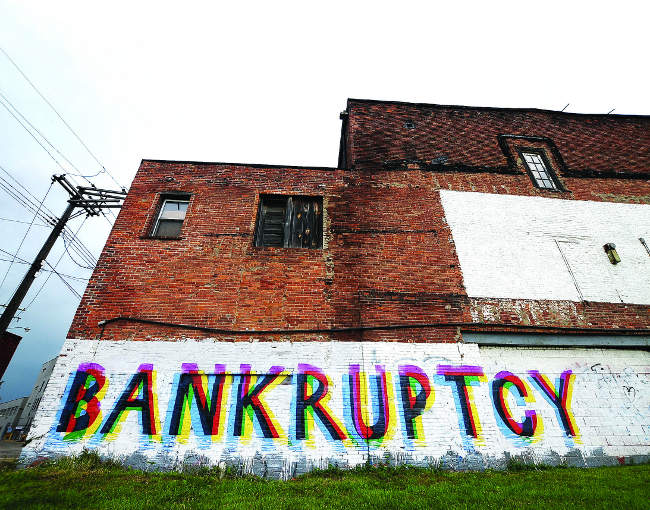 "Colorful graffiti on a wall in Detroit that says ""bankruptcy"""
