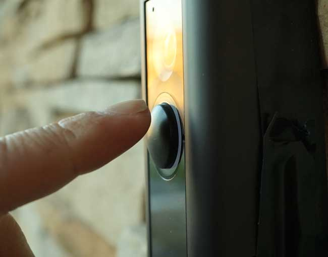 A finger about to push the button on a doorbell video camera