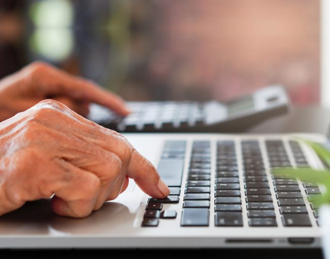 Elderly hands using a laptop keyboard