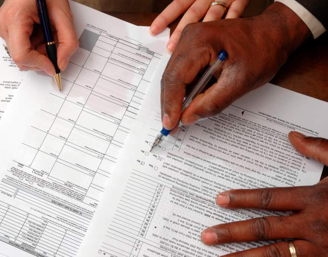 Two men filling out tax forms