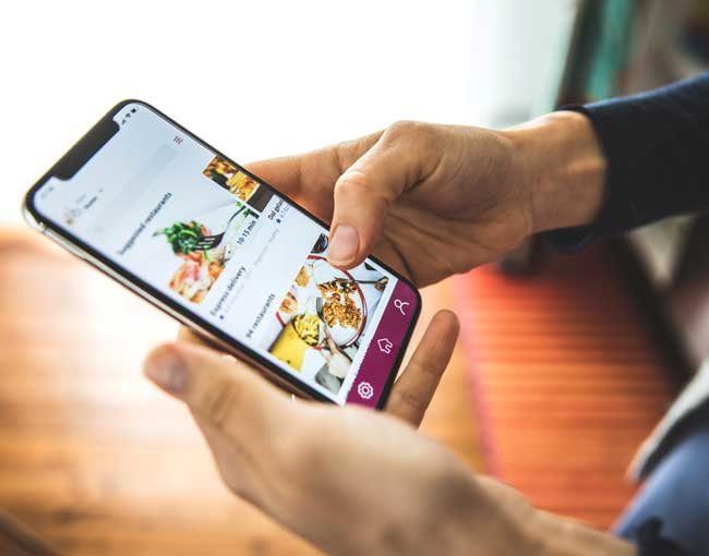 Someone using a food delivery app on a smart phone