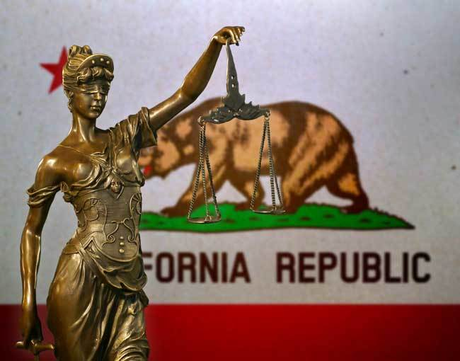 A statue of Justice in front of the California flag