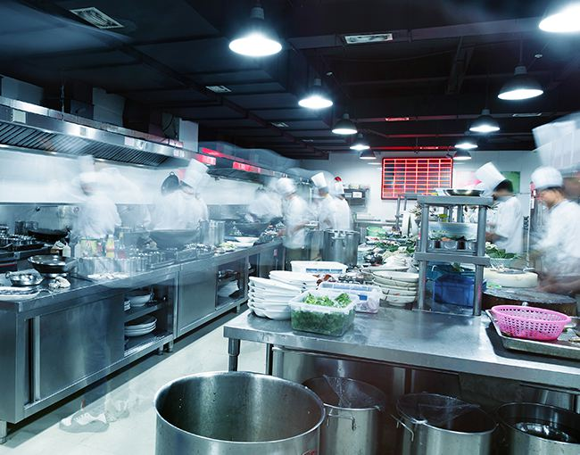 Photo of commercial kitchen with chefs blurred from movement