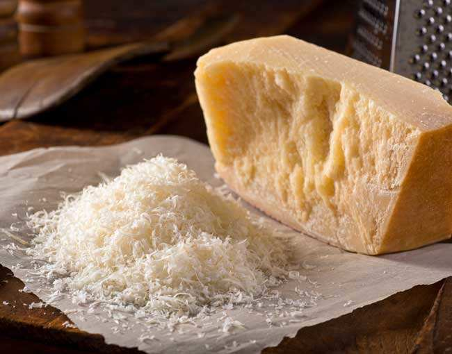 A block of parmesan cheese and grated cheese