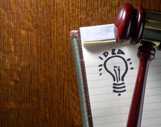 Gavel resting on notebook with idea sketch