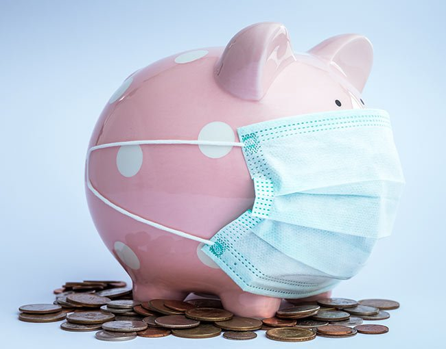 A piggy bank wearing a medical mask on top of coins