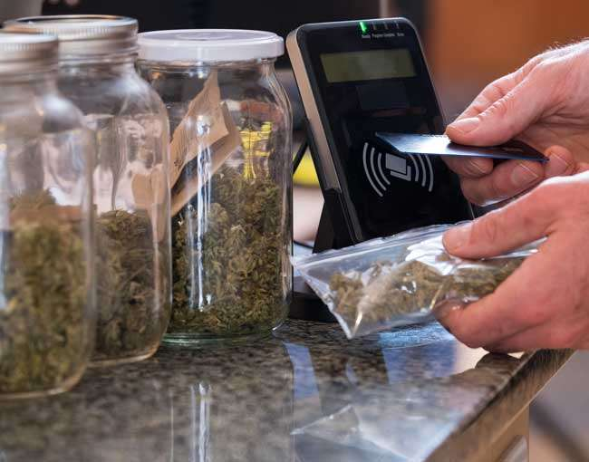 Someone purchasing legal cannabis using a credit card