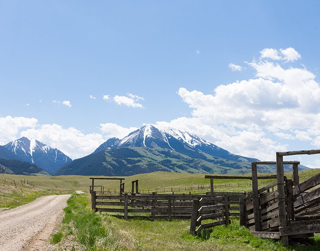 An old wooden corral with mountains in the background