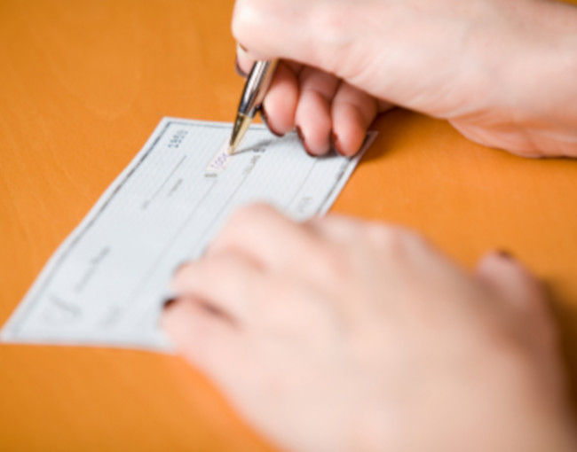 Woman's hands signing a check