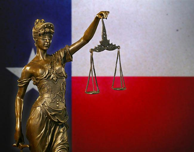 A statue of Lady Justice in front of the Texas flag