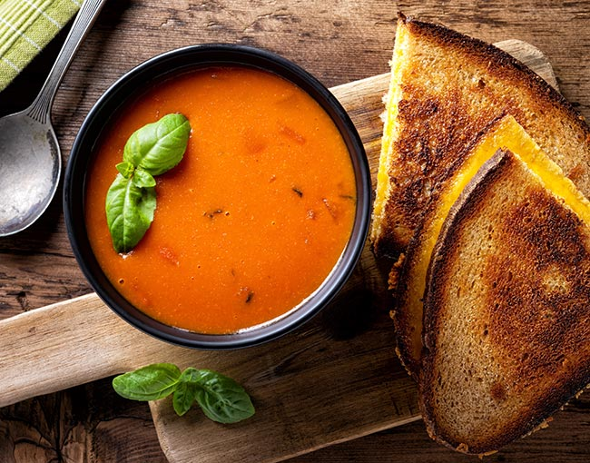 A bowl of tomato soup and a grilled cheese sandwich