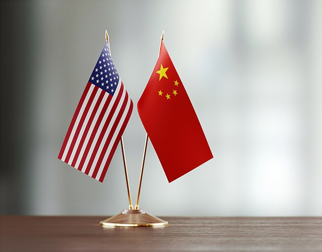 Small U.S. and China flags together on a desk