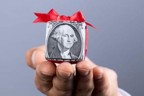 small gift parcel of money extended by a hand