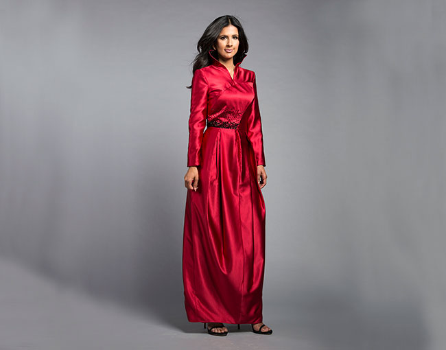 Model standing in a shiny red gown by designer Blue Meets Blue