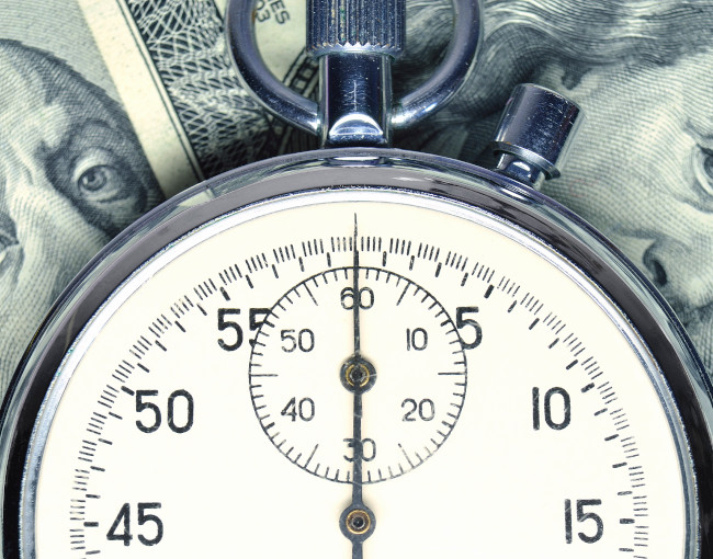 A stopwatch on a background of money