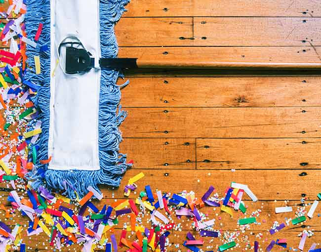 Broom cleaning up party confetti