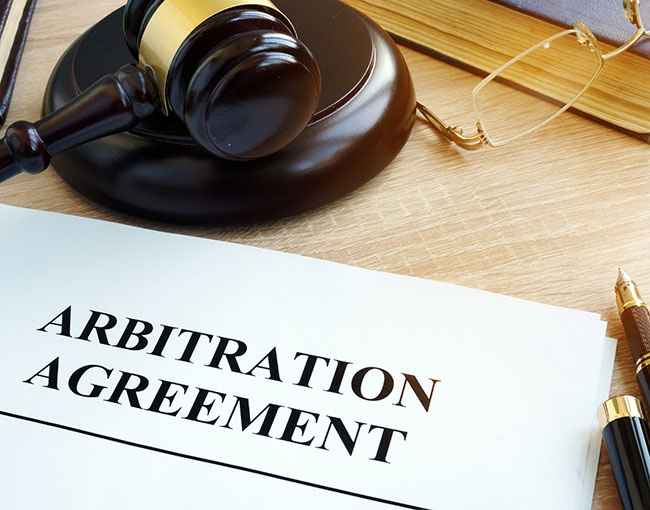 arbitration agreement with gavel and pen poised to sign it