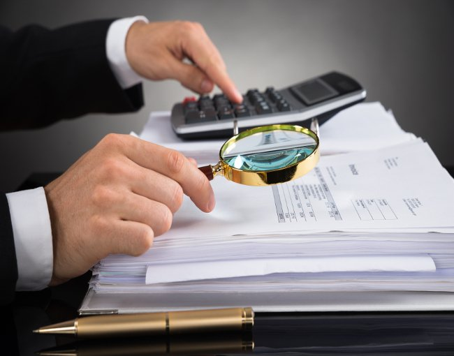 auditor reviewing financial documents with magnifying glass