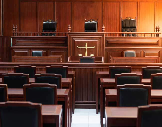 A photo of a courtroom with red wood furniture from the aisle