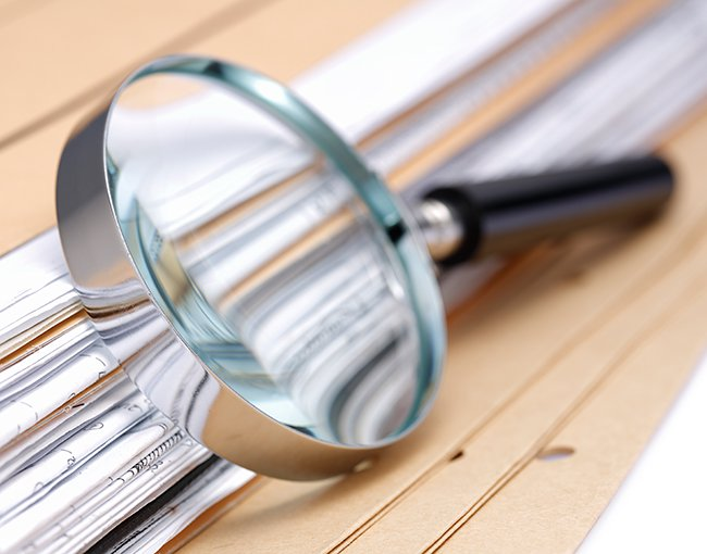magnifying glass rests on a stack of documents