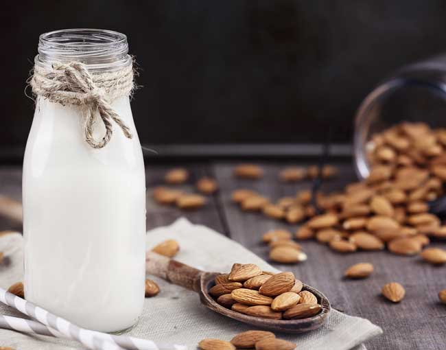 Photo of almond milk in a bottle, next to almonds