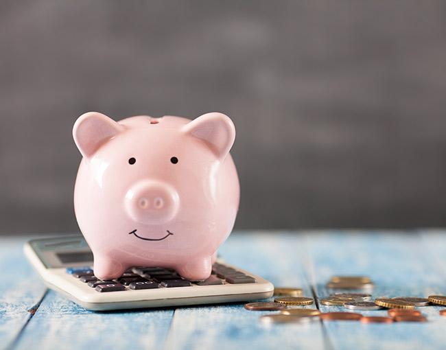 A piggy bank sitting next to a calculator