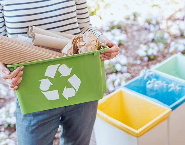 Person holding a recycling container full of paper products