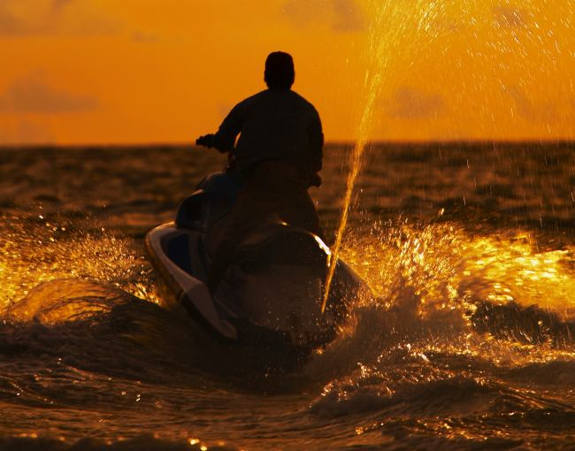 A person riding a personal watercraft at sunset