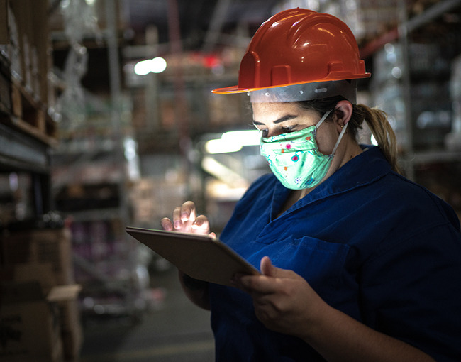 woman working in warehouse wearing hardhat and mask